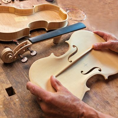 Luthier hands holding pieces of an unfinished violin on a workbench.