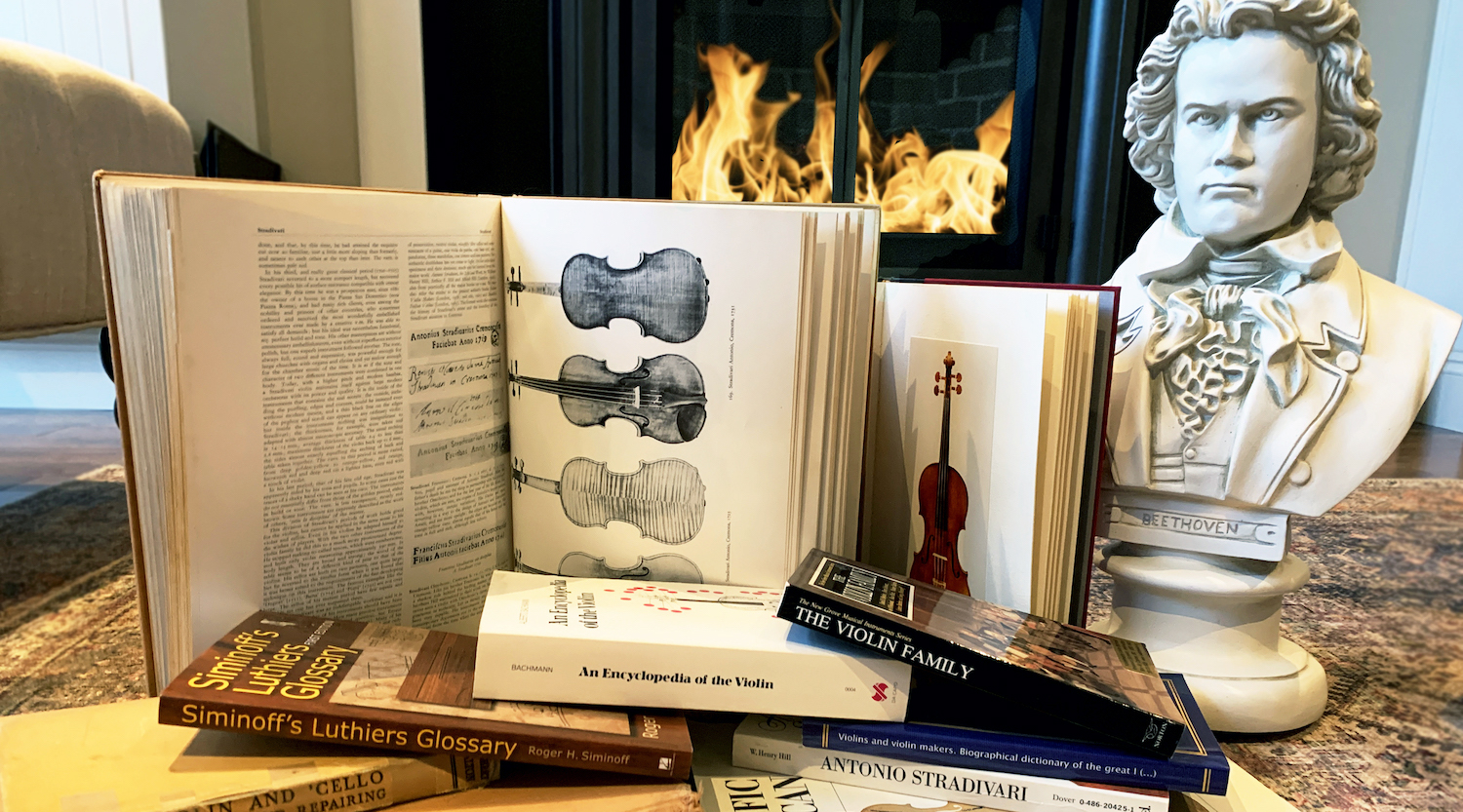stack of books and Beethoven bust in front of a fireplace