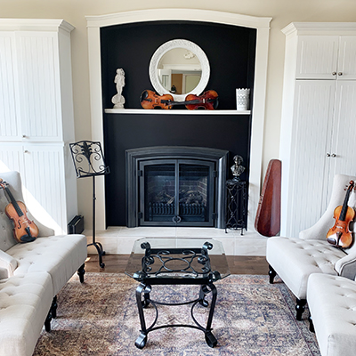 Fiddleheads' ornate heritage decorated studio main space with white wingback chairs, fireplace and violins