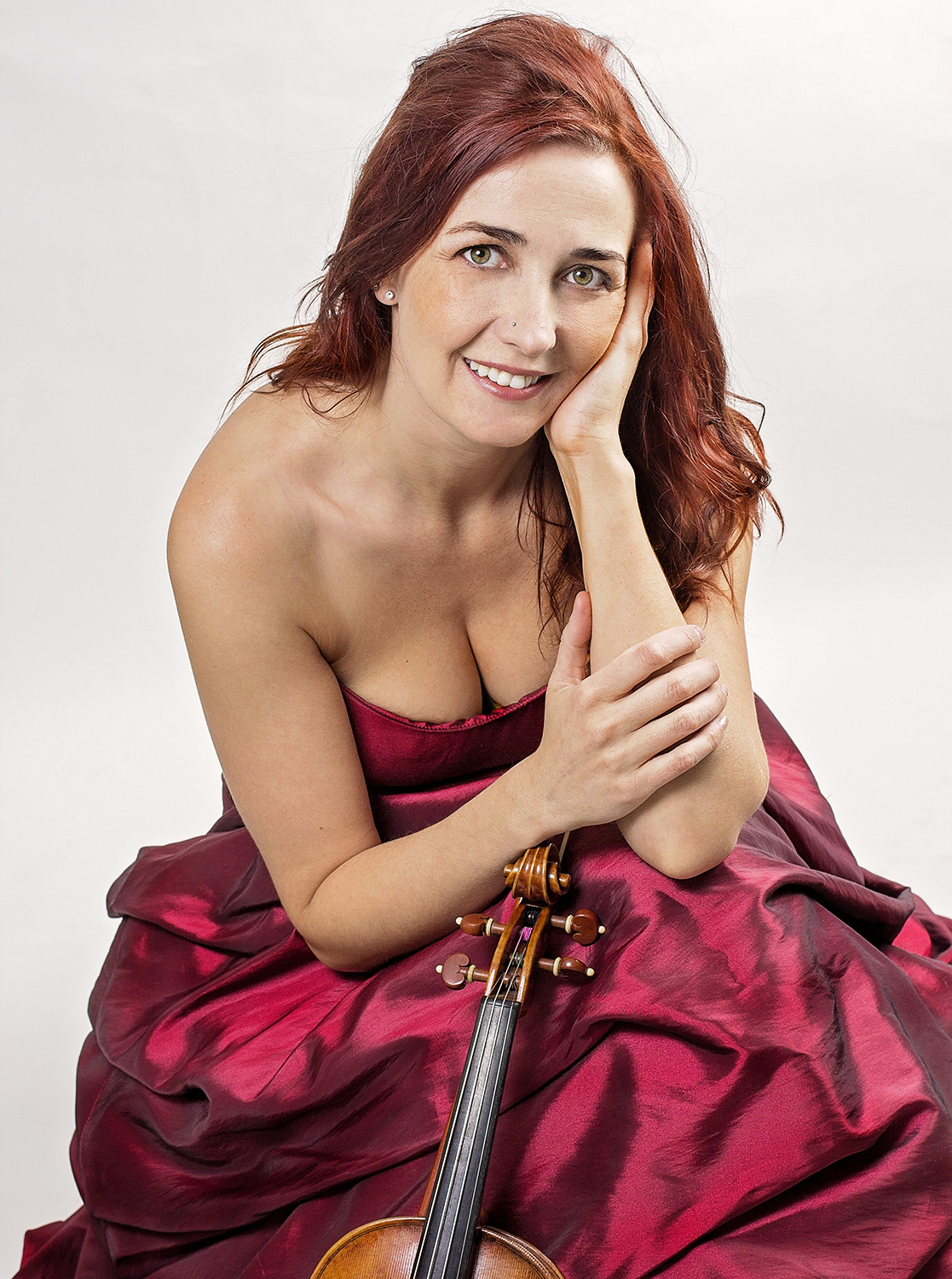 Rhiannon sitting in a red dress with her violin