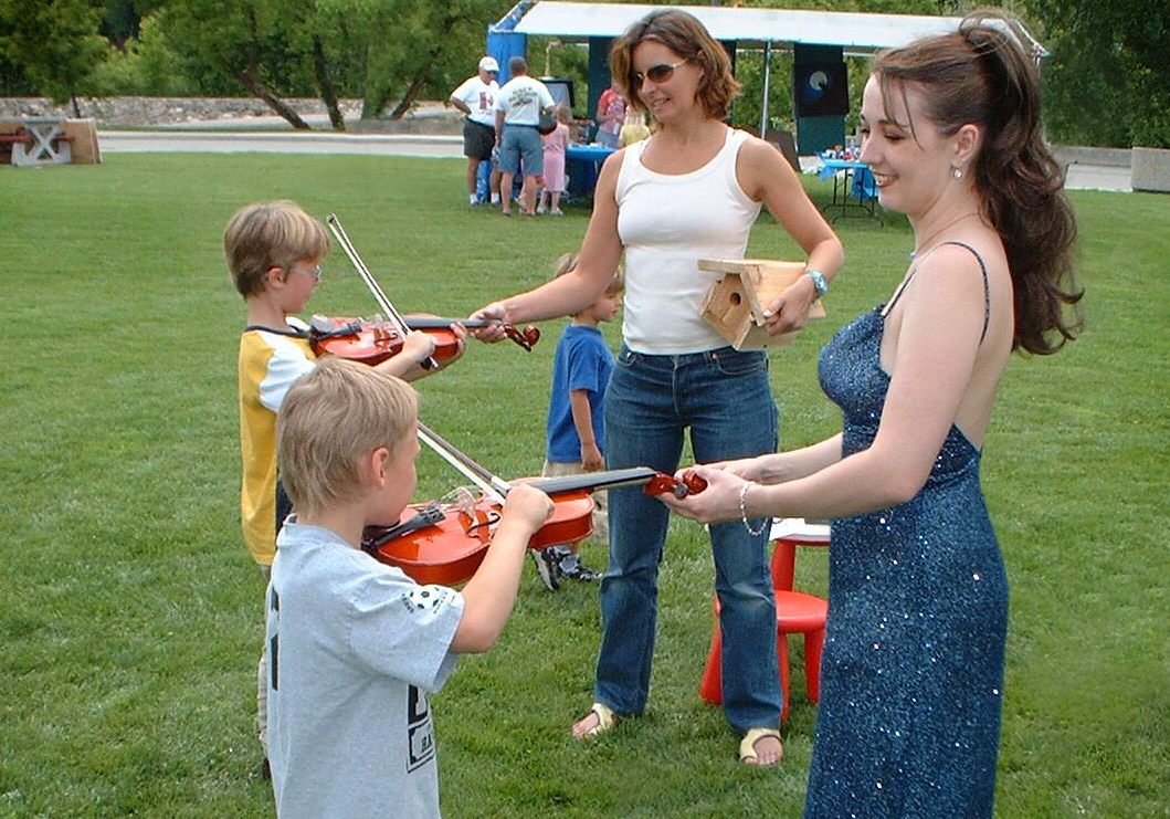 Rhiannon and a mom help children try the violin for the first time in a park