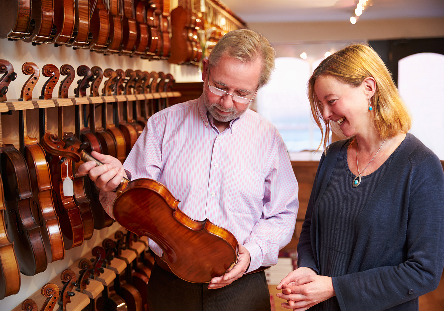 Man and woman in a violin shop holding a violin and smiling