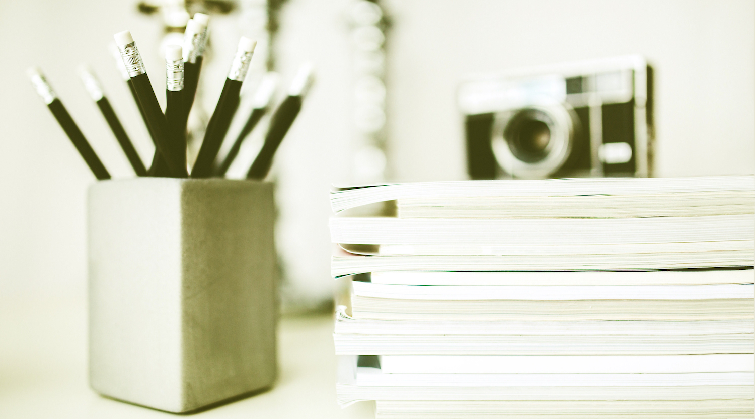 stack of magazines and cup of pencils