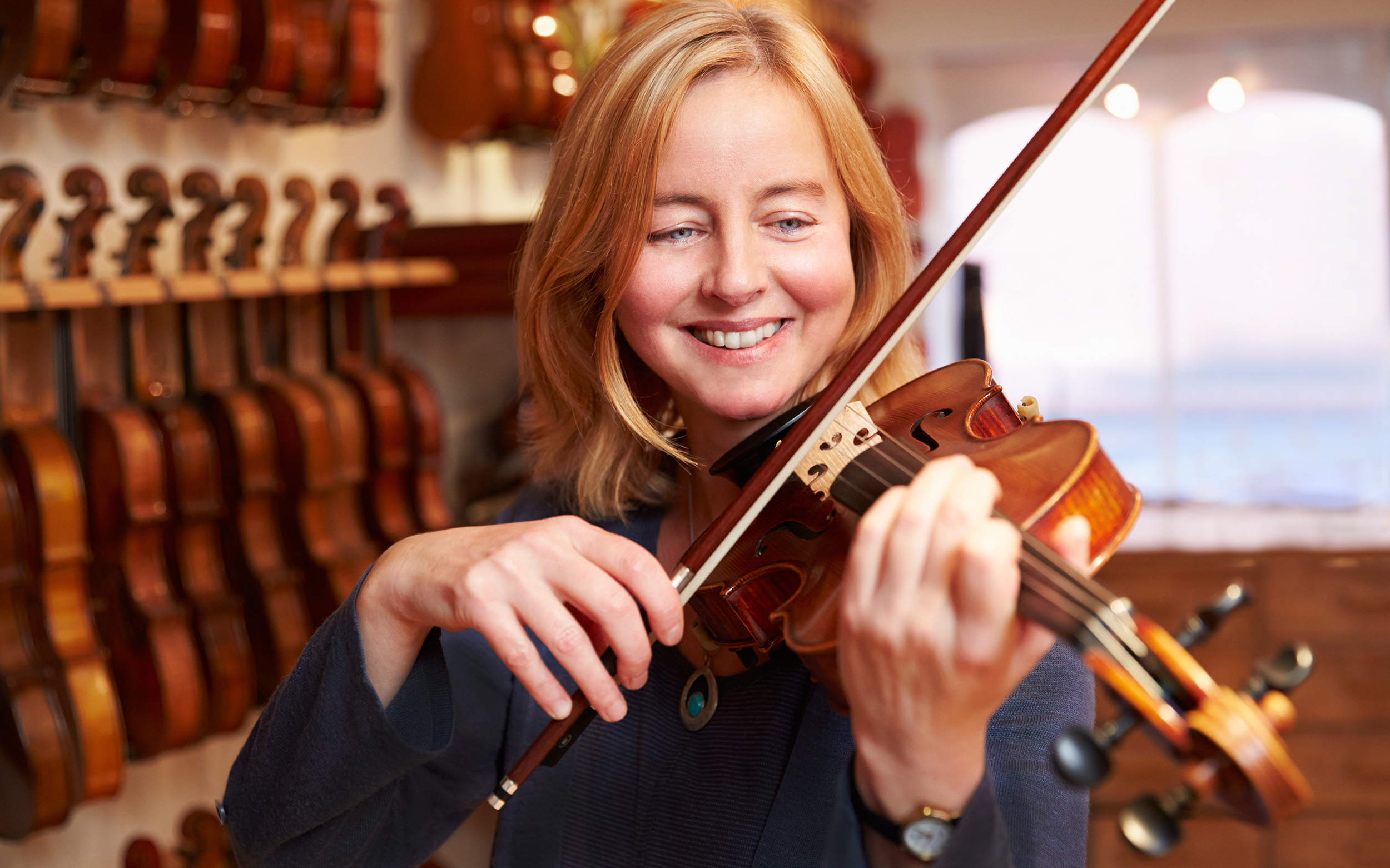 strawberry blond 40-something woman smiling while playing violin with many others in the background