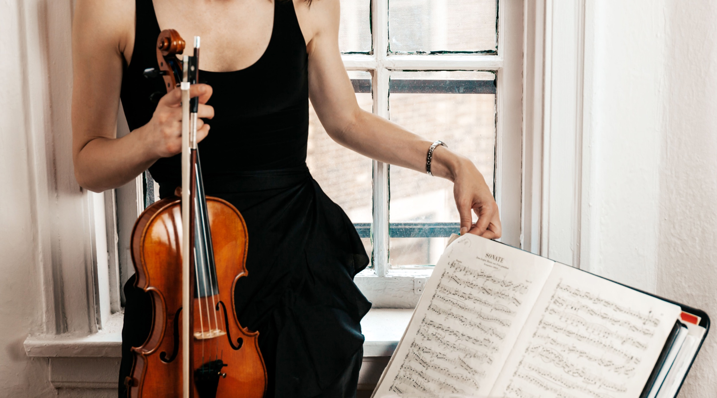 thin white woman in black dress holding her violin in front of an old painted white windowsill and preparing sheet music on a stand
