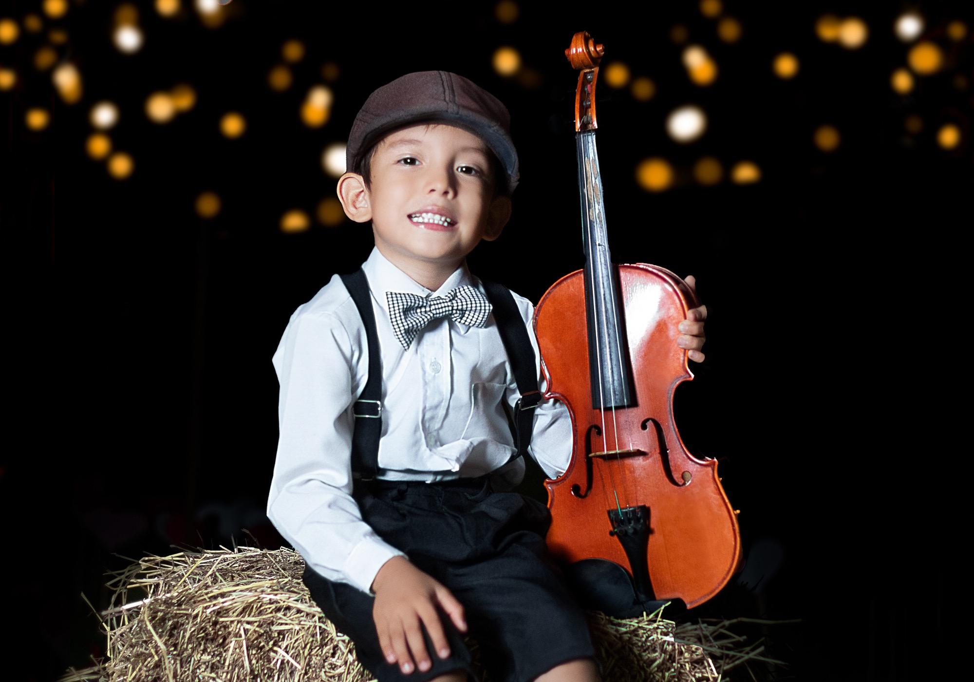 little boy sitting on a hay bale holding an oversized violin